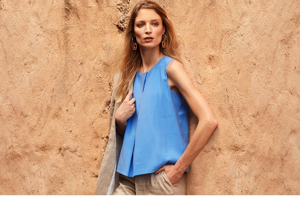 blauwe luchtige bloes met beige broek en vest