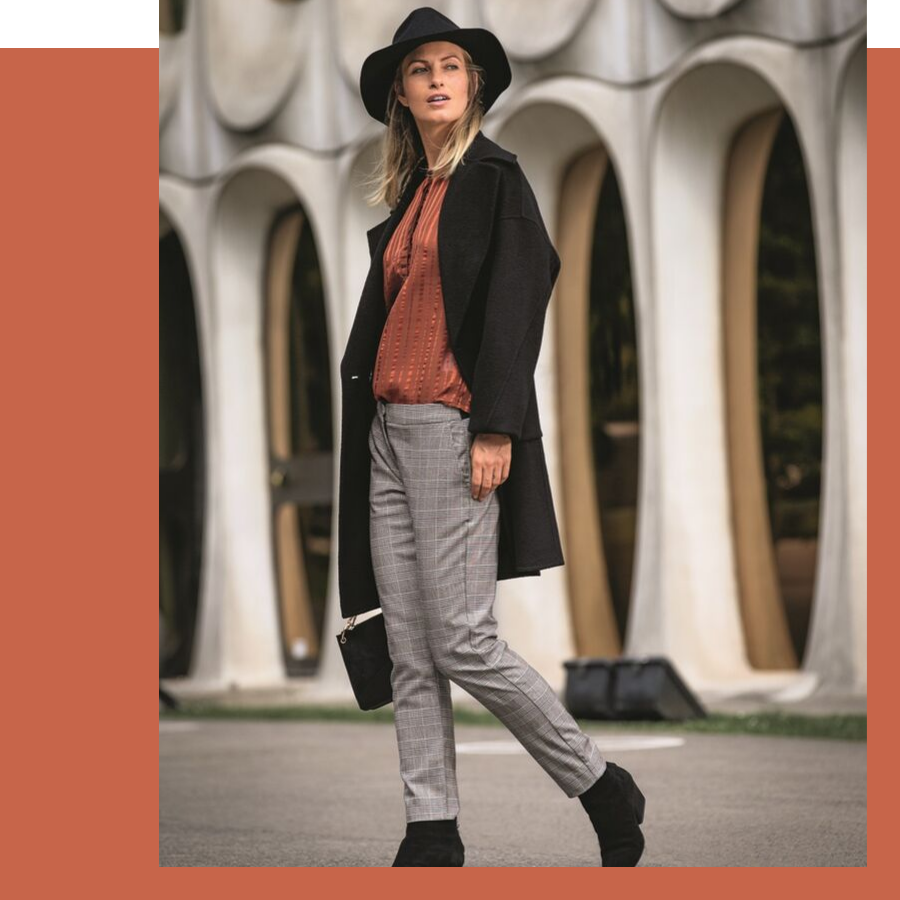 roestkleurige bloes met zwarte wollen mantel en geruite broek