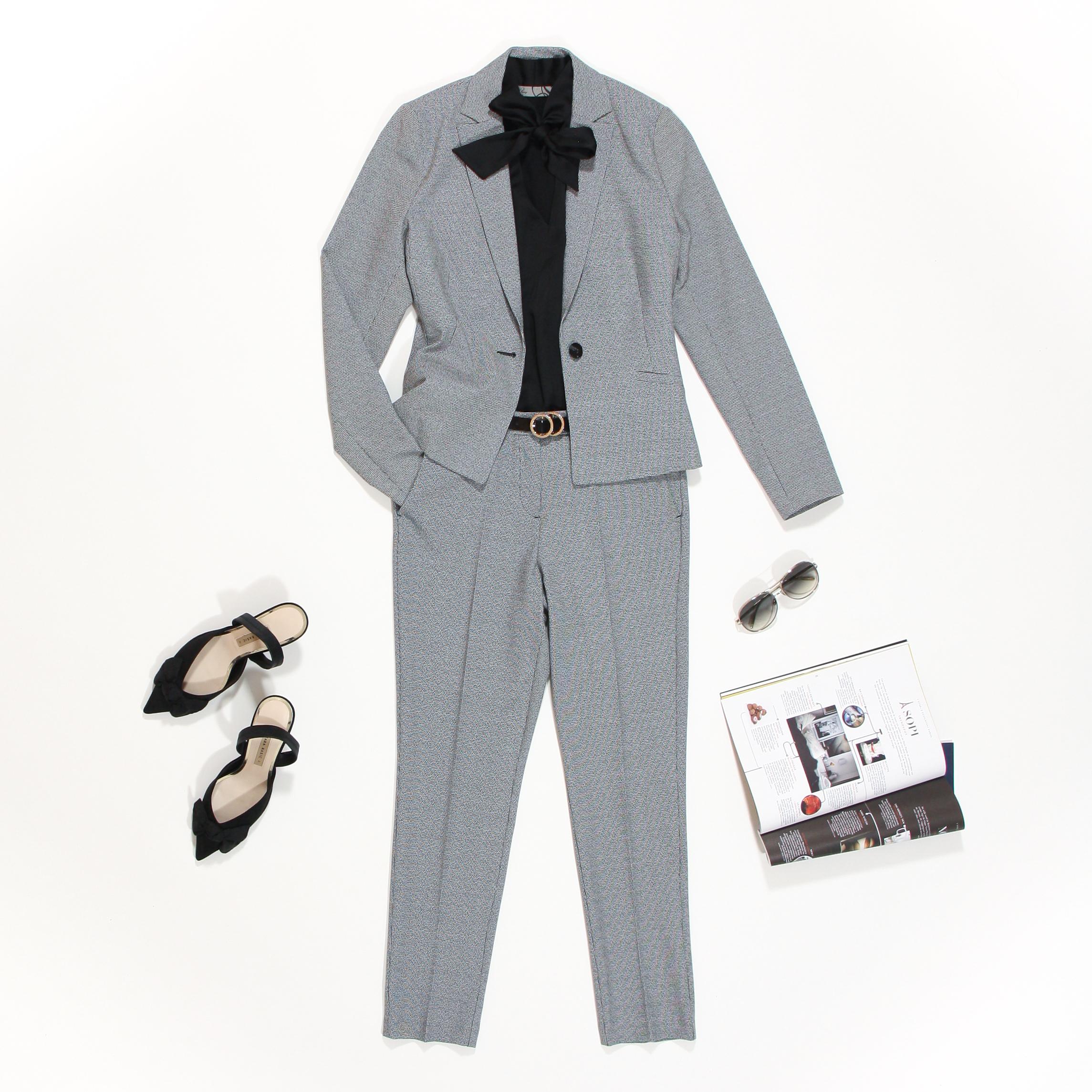 mantelpak met zwart witte ruitjes en zwarte blouse met strik